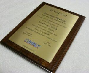 Dyplom wykonany w mosiądzu wykończenie grawerunku patynowe umieszczony na desce dębowej