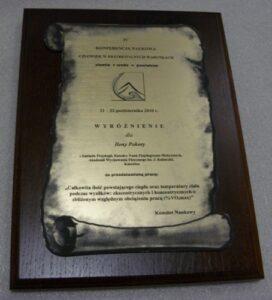 Dyplom grawerowany w formie zwoju w laminacie metalizowanym umieszczony na desce drewnianej