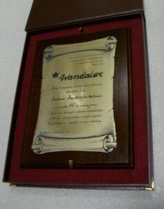 Dyplom grawerowany w formie zwoju w laminacie metalizowanym na desce dębowe w etui