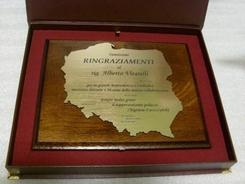Dyplom w kształcie mapy Polski wykonany z mosiądzu umieszczony na desce dębowej w etui