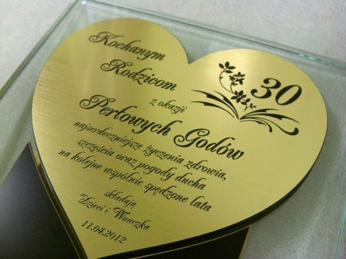 Dyplom w kształcie serca wykonany z laminatu metalizowanego umieszczony na statuetce szklaneju