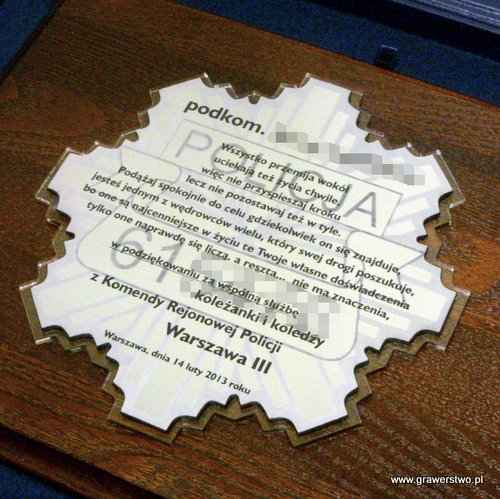 Dyplom grawerowany w formie gwiazdy policyjnej umieszczony na desce dębowej w etui