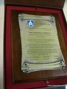 Dyplom w formie zwoju wykonany z laminatu metalizowanego na desce dębowej w etui