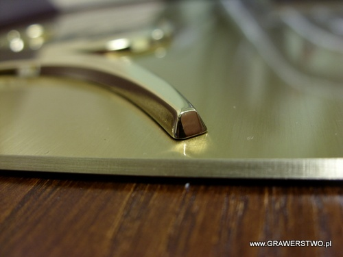 Fragment  nakładi złoconej na szyldzie mosiężnym