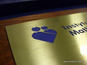 Logotyp grawerowany w mosiądzu wypełniony lakirem akrylowym w kolorze firmowym