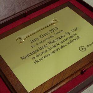 Dyplom grawerowany z mosiądzu szlifowanego z kuczem mosiężnym złoconym umieszczony na desce dębowej w etui