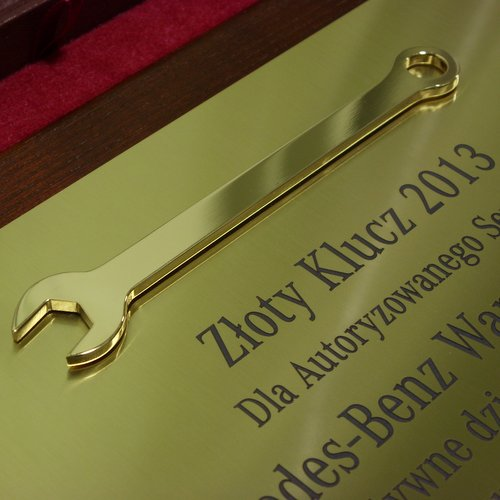 Klucz mosiężny złocony umieszczony na dyplomie