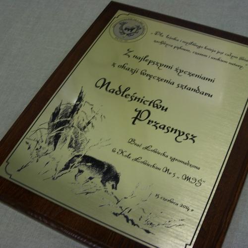 Dyplom grawerowany z laminatu metalizowanego umieszczony na desce dębowej
