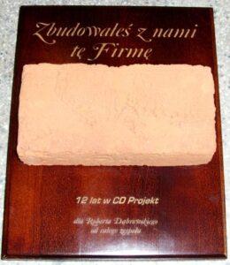 Ciekawy dyplom z cegłą na desce drewnianej