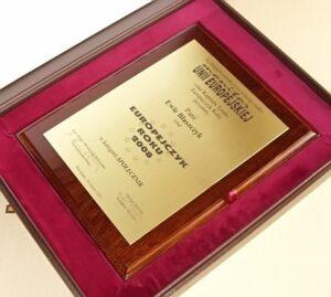 Dyplom Europejczyka Roku wygrawerowany w laminacie metalizowanym na desce dębowej w etui