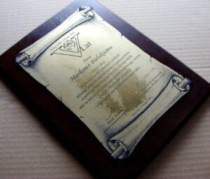 Dyplom grawerowany w formie zwoju wykonany z laminatu grawerskiego na desce drewnianej