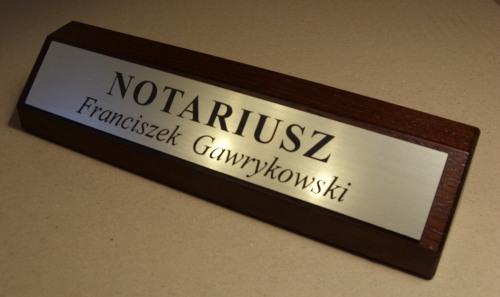 Identyfikator wygrawerowany w laminacie umieszczony na drewnianym klocku biurowymm