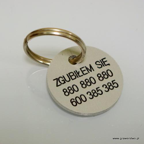 Przykład grawerunku wykonanego na aluminiowym identyfikatorze dla psa w kształcie koła
