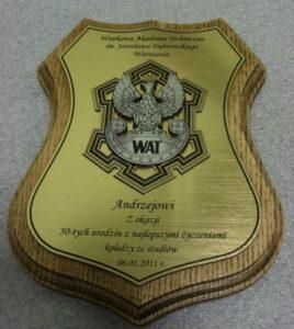 Pamiatka grawerowana w laminacie metalizowanym na podkładzie drewnianym logo WAT jako nakładka