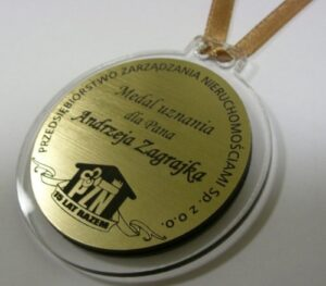 Medal grawerowany na laminacie metalizowanym na podkładzie z plexi bezbarwnej