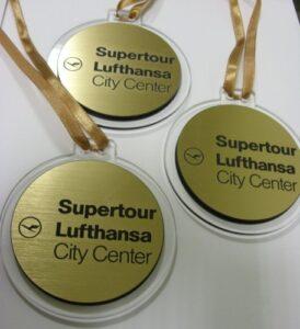 Medale grawerowane na laminacie metalizowanym na podkładzie z plexi bezbarwnej