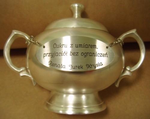 Tabliczka-mosiądz polerowany w kolorze srebrnym zamocowana na srebrnej cukiernicy